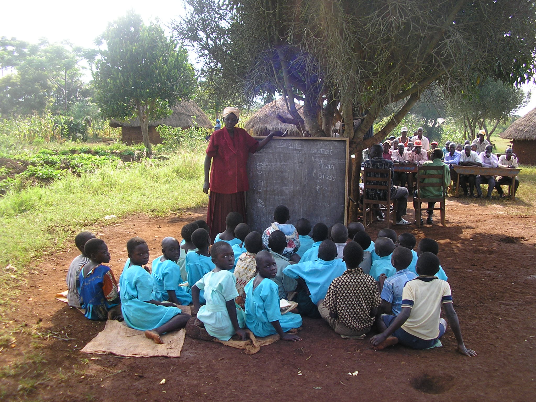 Many children have lessons outside, Seated on the dirty ground under the shade of trees