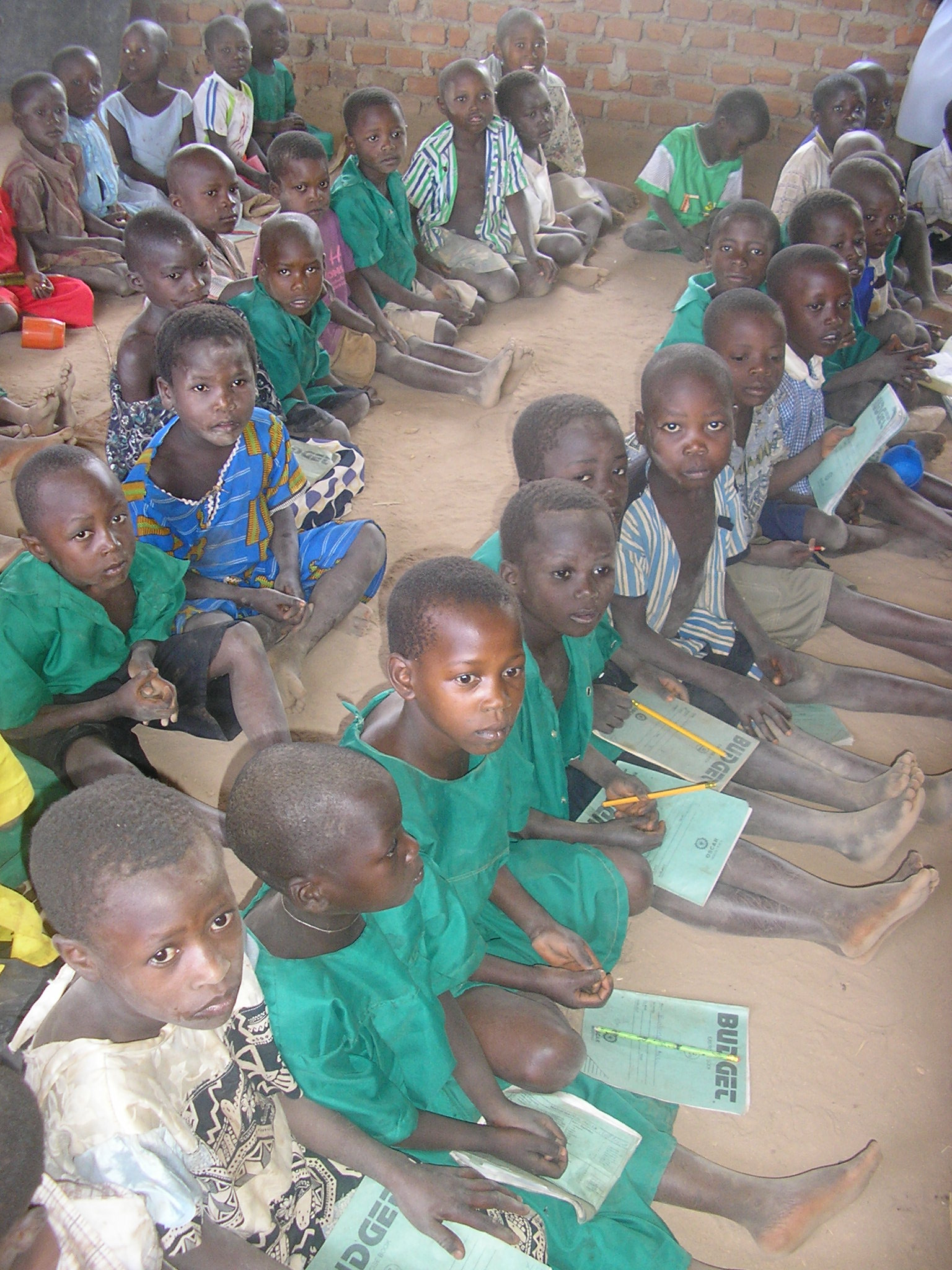Due to lack of desks, children are forced to sit on dirt floo, or pathetically, a brick!
